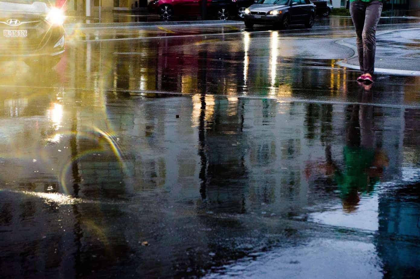 Eine von Wasser bedeckte Straße, auf der sich Autos spiegeln