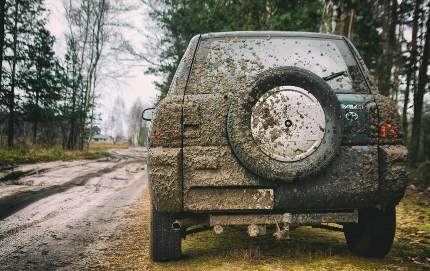 Verschmutzter Jeep am Straßenrand